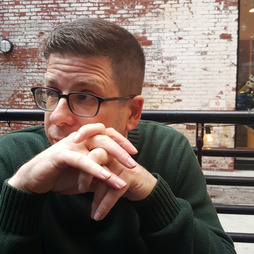 Image of Mike Caulfield at a table with his hands crossed looking his right contemplatively.